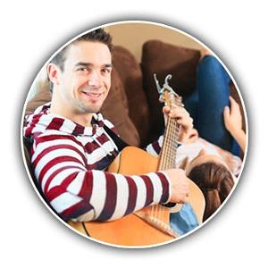 Mann und Frau mit Gitarra auf Sofa